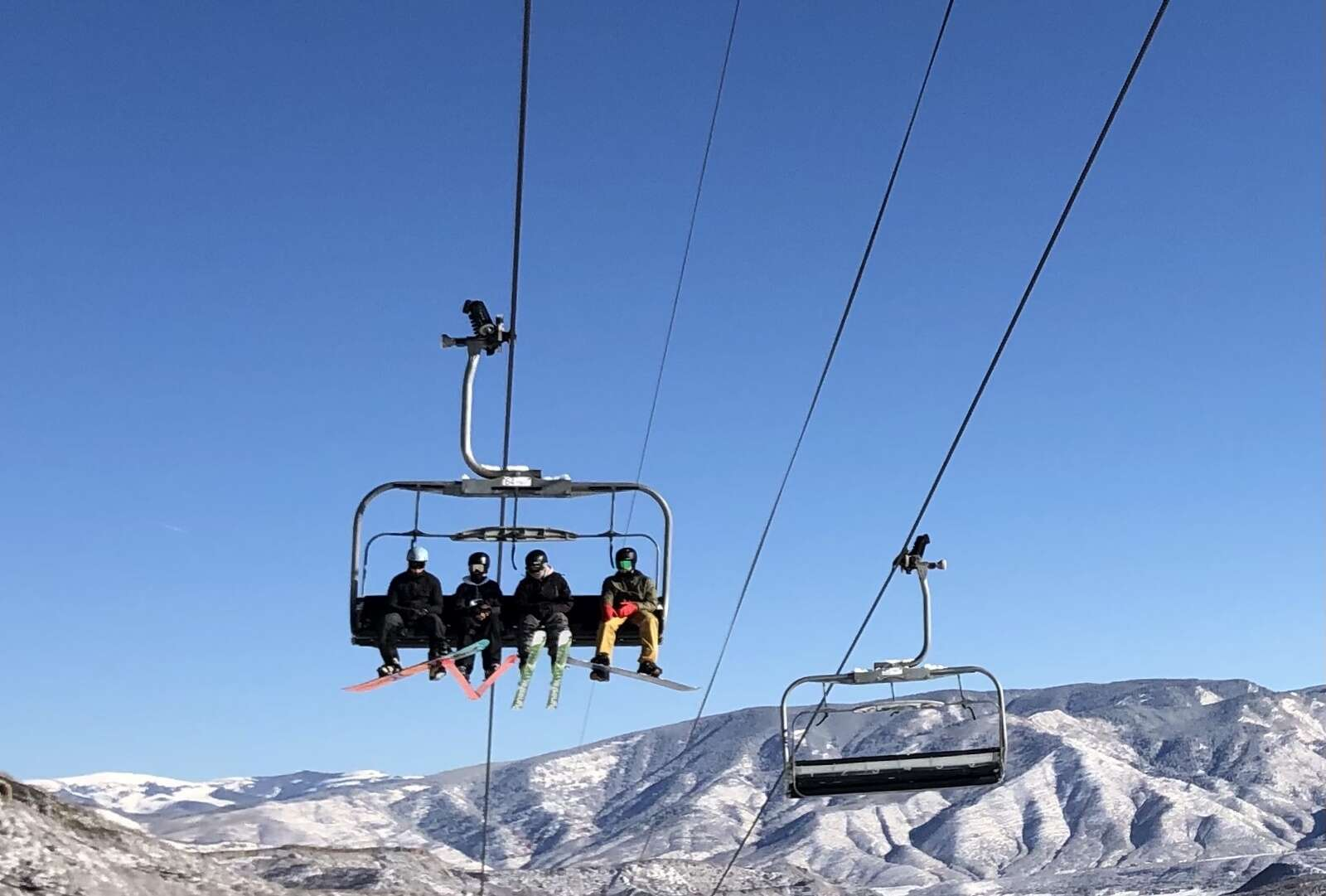 Four skiers ride the Village Express chairlift during a mellow opening day at Snowmass on Nov. 25, 2020.