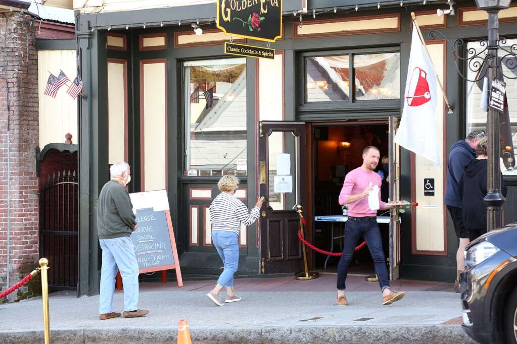 Folks keep socially distant as they place and pick up their curbside to-go orders at The Golden Era Lounge in downtown Nevada City April 19. | Photo: Elias Funez