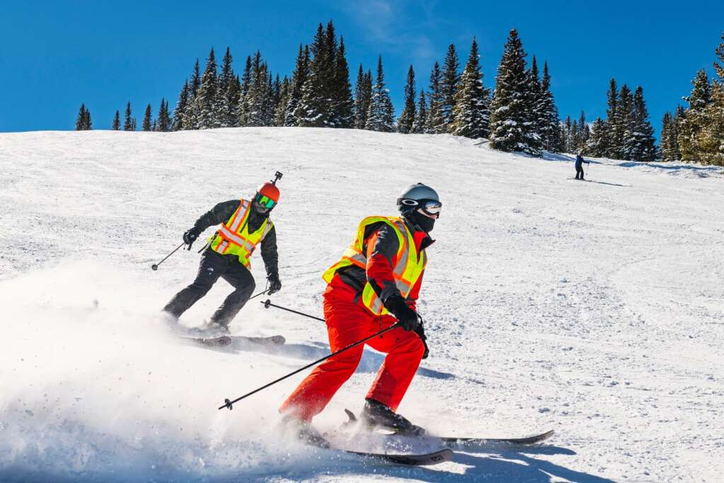 Paul Hibben, left, guides friend Chad Foster down a run off of the Big Burn lift in Snowmass on Monday, Feb. 22, 2021. (Kelsey Brunner/The Aspen Times)