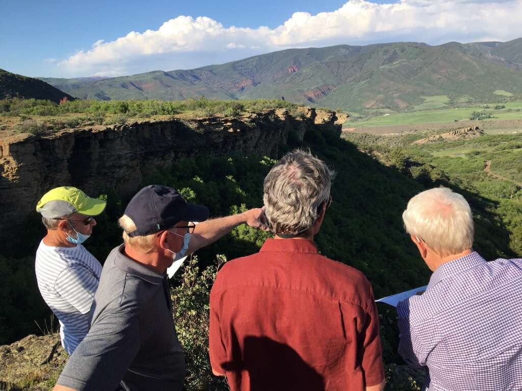 Snowmass Village Town Councilmen Bob Sirkus (far left) and Tom Fridstein look at a map of the Cougar Canyon with Mayor Bill Madsen and attorney David Myler during a site visit on Monday, June 7, 2021. Myler represents land owner David Bonderman, who is seeking an extension of vested property rights through 2050 for the Cougar Canyon and neighboring Cozy Point Ridge subdivisions.   Kaya Williams/The Snowmass Sun
