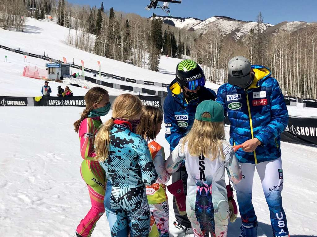 U.S. Ski Team members River Radamus (left) and Luke Winters sign autographs for young NASTAR competitors after the Platinum division finals on April 10 at Snowmass Ski Area. | Kaya Williams/The Aspen Times