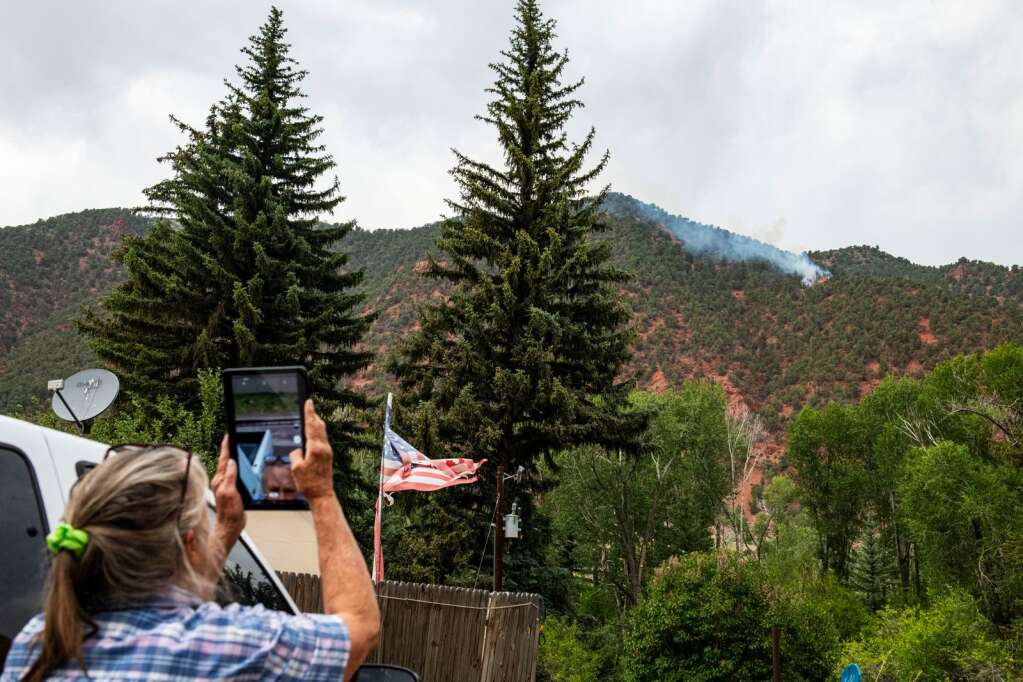 Toni Kronberg takes photos of a fire burning across the river from her home off Highway 82 near mile maker 28 in Old Snowmass on Friday, June 18, 2021. Kronberg hurried home from work in El Jebel to prepare to evacuate with her dogs if the fire came closer. (Kelsey Brunner/The Aspen Times)