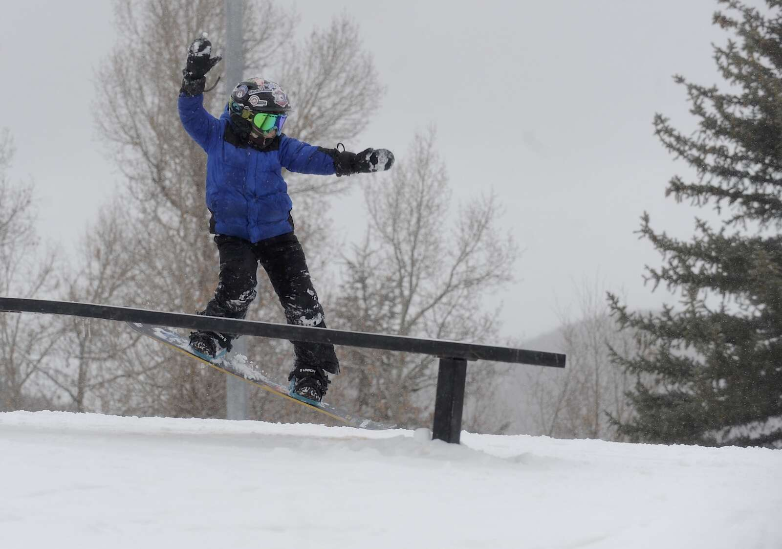 Adam Lilly gracefully dismounts a rail at a free, public rail jam put on  at Howelsen Hill on Saturday.