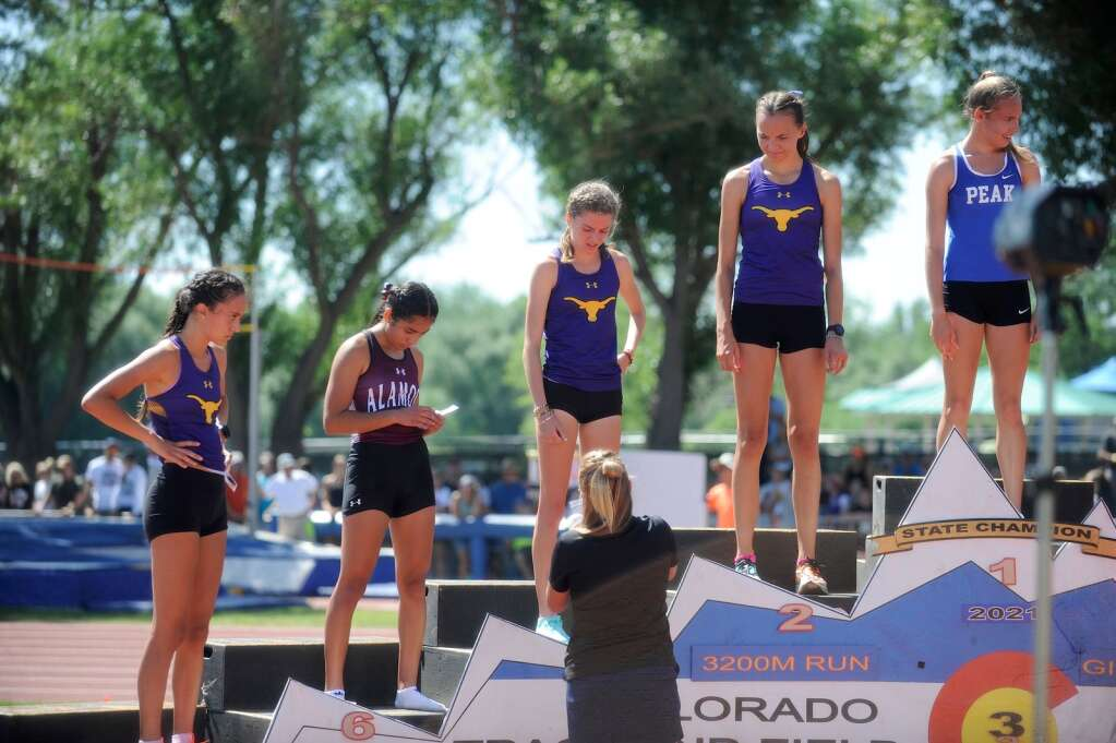 Basalt High School sophomore Katelyn Maley, second from right, watches as senior teammate Sierra Bower receives her award after the Class 3A girls' 3,200-meter run on Friday, June 25, 2021, at the state championship meet in Lakewood. Maley finished second and Bower fourth. Photo by Shelby Reardon/Steamboat Pilot & Today.