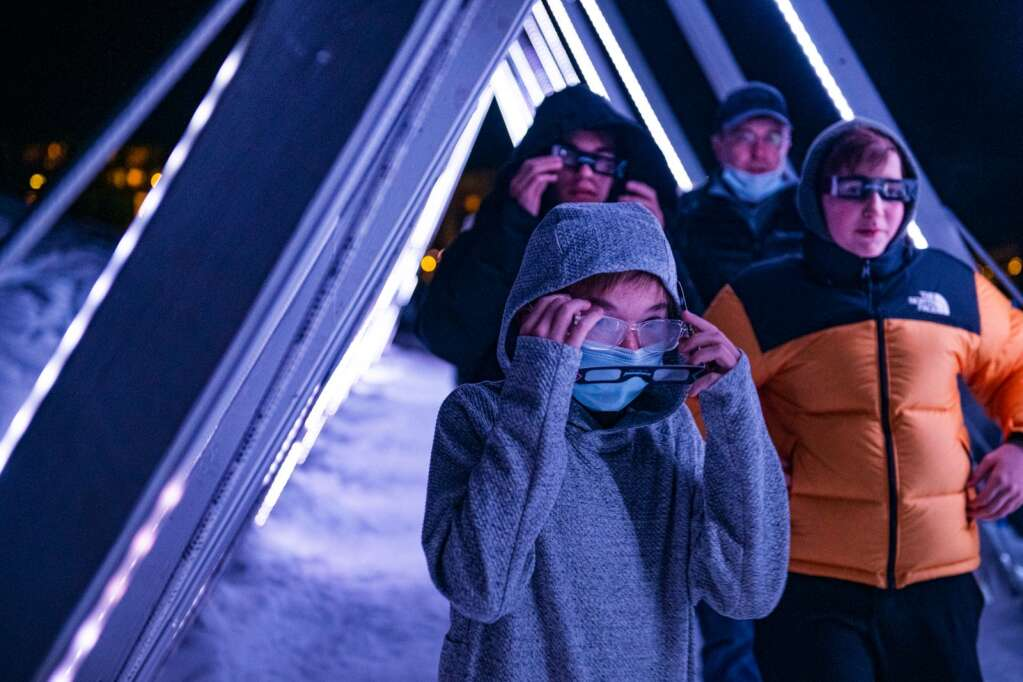 A family walks through the Snowmass Luminescence in the last hour of the year after the fireworks display on New Years Even on Thursday, Dec. 31, 2020. (Kelsey Brunner/The Aspen Times)