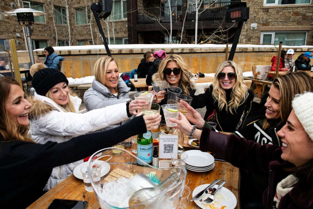 A group of women make a toast on the outside patio of Dante at The Snow Lodge at the base of Aspen Mountain on Friday, Jan. 22, 2021. (Kelsey Brunner/The Aspen Times)