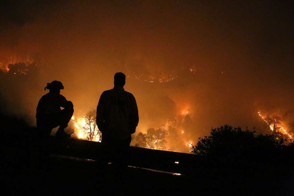 Cal Fire firefighters watch over the Jones Fire from Highway 49 near Rush Creek, after initiating a firing procedure early in the morning Tuesday Aug. 18. The procedure helped reduce fire fuels before a full day of fighting the fire lay ahead. | Photo: Elias Funez