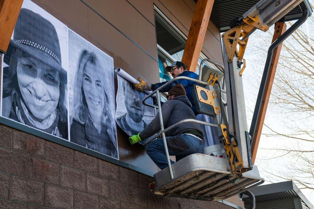 """The CORE installation crew hangs the individual posters depicting 89 participants of the """"Stories of Climate Change/Historias del Cambio Climatico"""" mural and storytelling project at the Colorado Mountain College campus in Aspen on Monday, Feb. 22, 2021. (Kelsey Brunner/The Aspen Times)"""