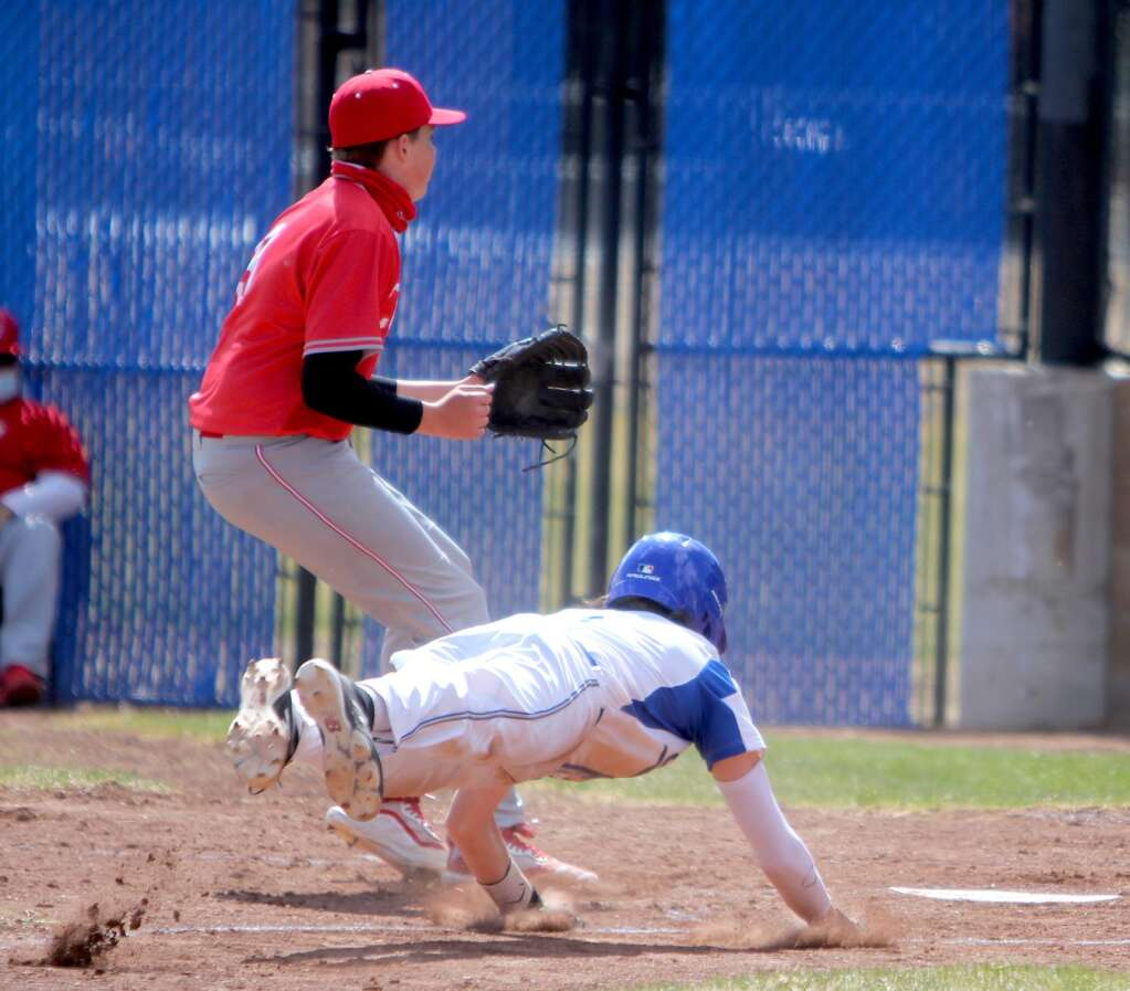 Nico Wagner dives safely into home plate.