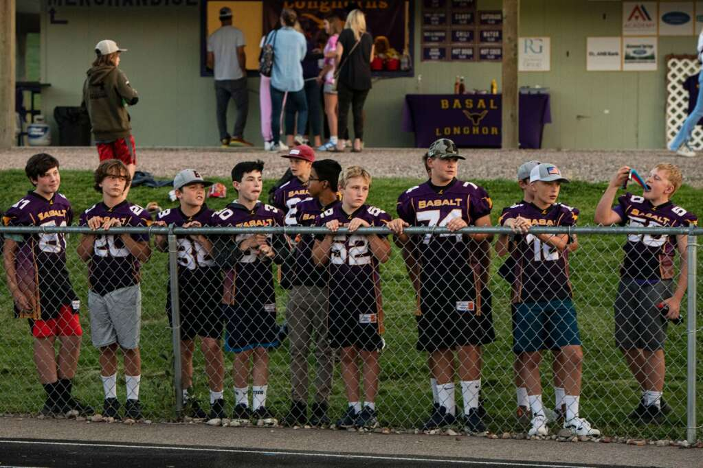 Young Basalt athletes watch as the Longhorns play their season opener against Woodland Park at Basalt High School on Friday, Aug. 27, 2021. (Kelsey Brunner/The Aspen Times)