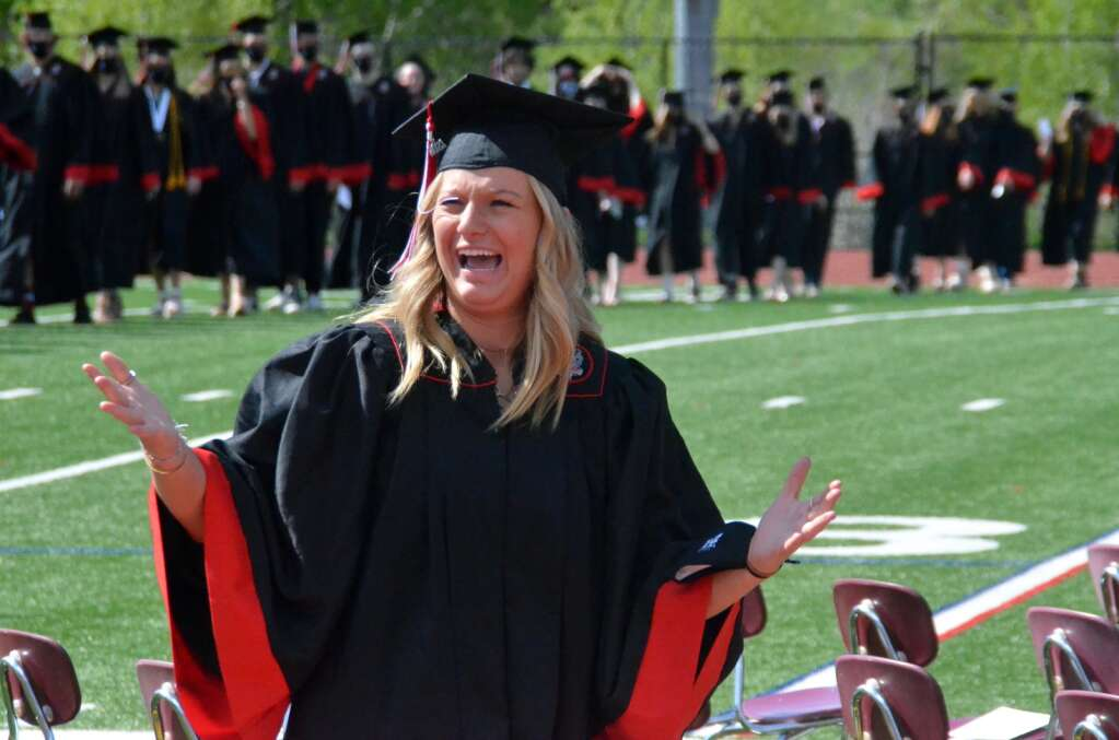Rose Epstein responds to her fans in the cheering section while walking into graduation. (Photo by Bryce Martin)