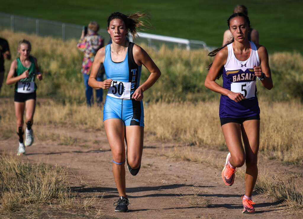 Cross country runners from Coal Ridge and Basalt, Araceli Ayala and Ava Lane, battle for second place during Friday's meet hosted by Coal Ridge at VIX Park in New Castle. |Chelsea Self / Post Independent