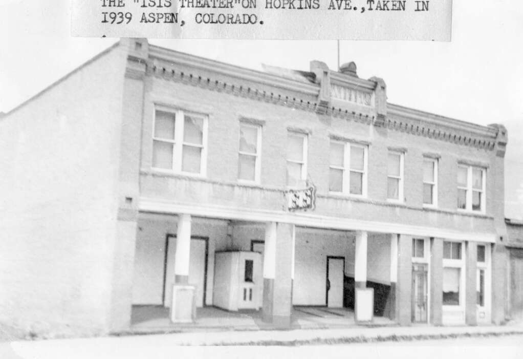 One b/w photograph of the exterior of the Isis Theater/ Webber Block on Hopkins Avenue.  The front of the building where the Isis is has no doors - they are recessed in the building.  Caption on top dates it to 1939. (Aspen Historical Society)