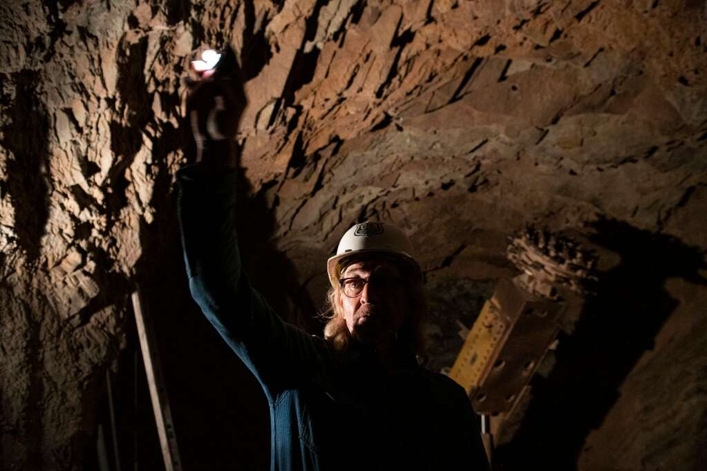 Robert Congdon lights up a far tunnel in his White Banks Alabaster Mine where a continuous miner sits idled outside of Redstone on Thursday, July 29, 2021. (Kelsey Brunner/The Aspen Times)