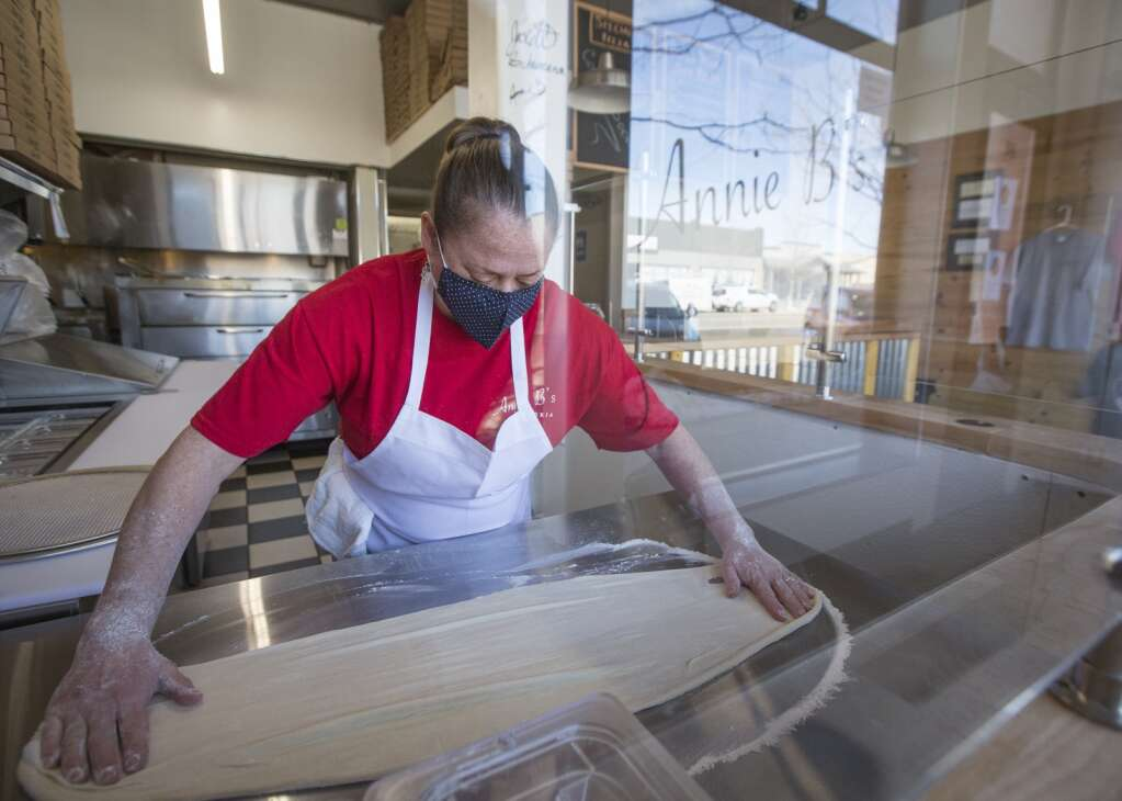 Anne B. Woodward stretches out pizza dough as she prepares a pizza at her pizzeria, Annie B.'s Pizzeria, in Coalville on Wednesday, March 3, 2021. (Tanzi Propst/Park Record)