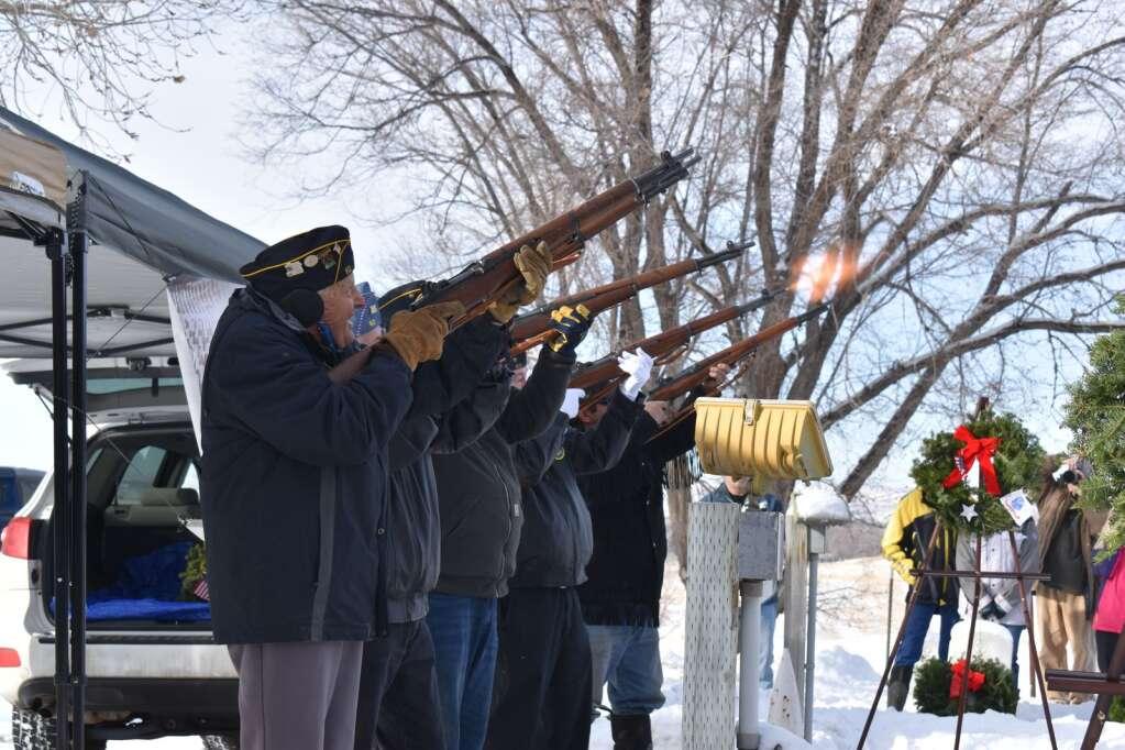 Members of the honor guard fire a volley of three shots Saturday.