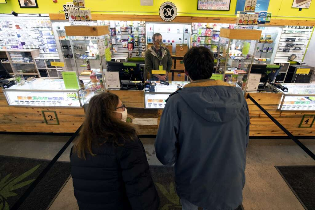 Nick Donovan, center, a manager at Altitude Organic Cannabis in Dillon, talks with customers while they stand stand 6 feet away from the counter on Tuesday, Feb. 16. | Photo by Jason Connolly / Jason Connolly Photography
