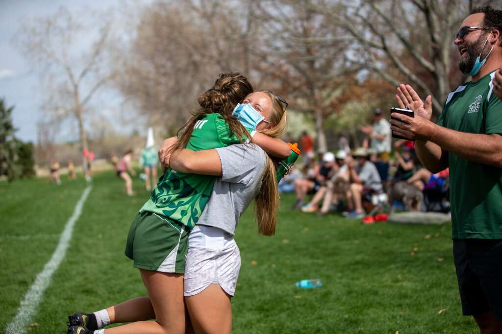 Former Summit rugby state champion Cassidy Bargell joyfully congratulates Bryton Ferrari on the game-winning score against Monarch at the high school rugby state championships on Saturday, May 1, 2021, at Cook Park in Denver, Colo. As the Tigers won their first game, tied the second, and claimed victory in the third, the Summit High girls rugby team clinched their 13th-straight state championship title. | Photo by Liz Copan  /Studio Copan