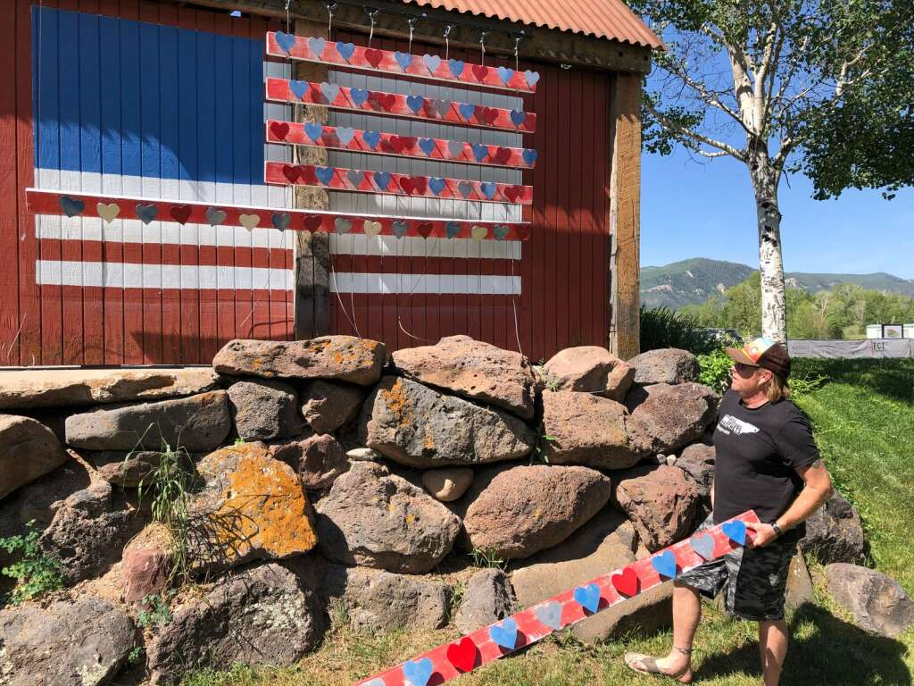 """John Przonek works on his 3D mural, """"Meeting of the heARTS,"""" in Basalt on Monday, June 7.   Scott Condon/The Aspen Times"""