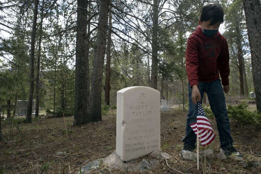 Nicholas George, a fourth grader from Upper Blue Elementary School, places a U.S. flag at the grave site of a veteran at Valley Brook Cemetery in Breckenridge on Friday, May 28. George and his fourth grade classmates placed flags at the graves of veterans throughout the cemetery in preparation for Memorial Day. | Jason Connolly / Jason Connolly Photography