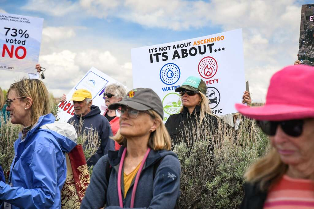 Opponents of the Ascendigo property hold signs in protest of the development during the Garfield County Commissioners site visit in Missouri Heights on Tuesday afternoon. |Chelsea Self / Post Independent