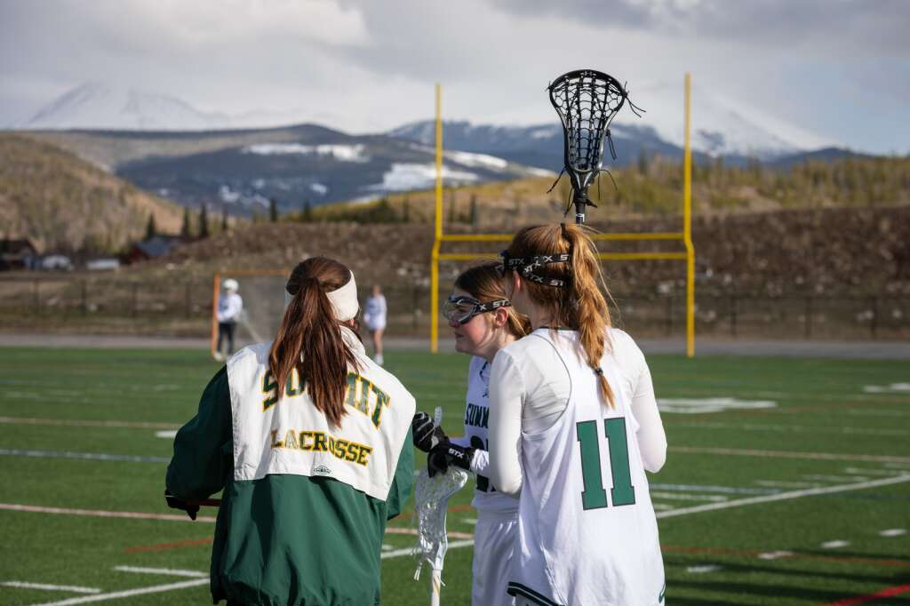 Kallie MacDonald (right) assesses the actin from the sideline during the Summit High School varsity girls lacrosse team's 14-4 loss to Eagle Valley at Summit High School in Breckenridge on Tuesday, May 11, 2021. | Photo by Lucas Herbert / Lucas Herbert Media