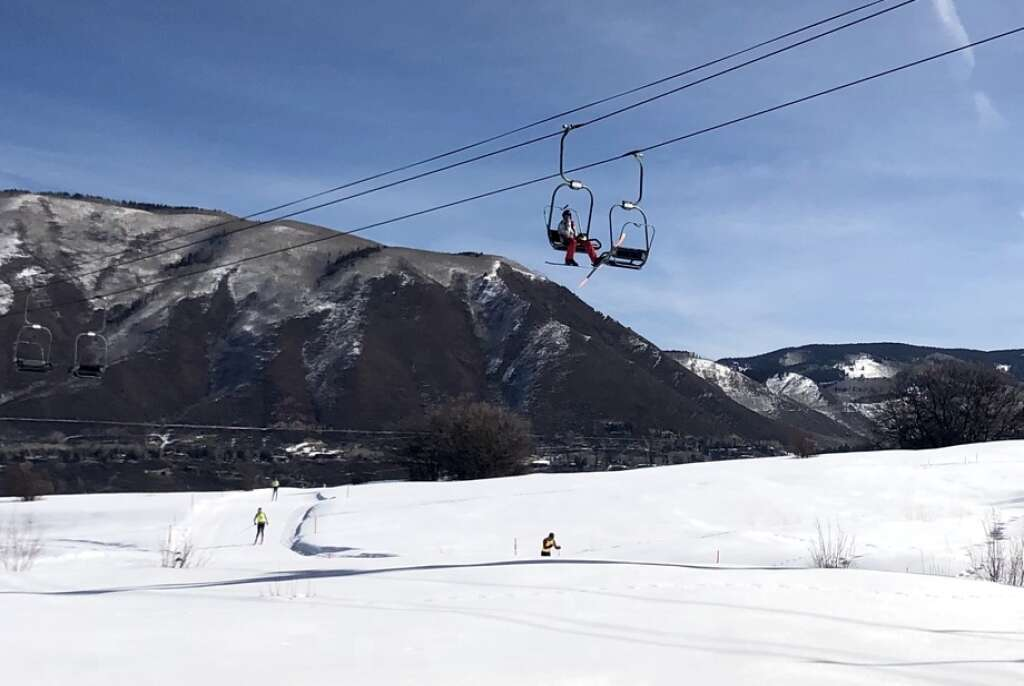 A downhill skier rides the Five Trees private charlift near the Aspen Valley Ski and Snowboard Club as cross-country skiers compete in the Owl Creek Chase in Aspen on March 7, 2021. | Kaya Williams/The Aspen Times
