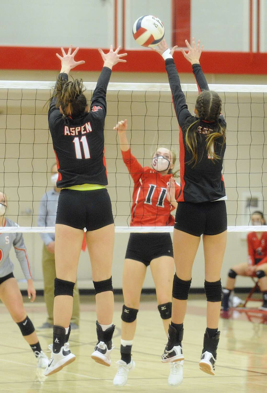 Steamboat Springs player Sophie Diehl sneaks the ball between a block by Aspen's Bella Haneman, left, and Sadie Bayko during a game on Thursday night. (Photo by Shelby Reardon)