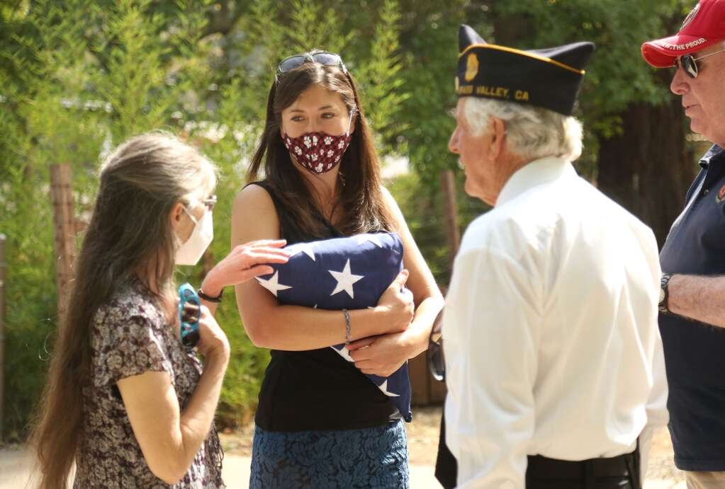 Misti Wood (center) with mother Robin Wood, are approached by members of the American Legion Post 130 following Saturday's Remembrance Day ceremony Sept. 28. Wood held a service flag in memory of father/husband Dale Wood, who was a Navy Seabee that died in May and had yet to have a memorial service due to Covid-19. | Photo: Elias Funez