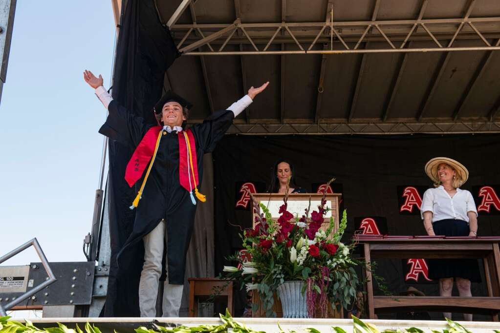 An Aspen High School graduate lifts his hands up as his fellow classmates cheer him on as his name is called during the 2021 commencement ceremony on Saturday, June 5, 2021. (Kelsey Brunner/The Aspen Times)