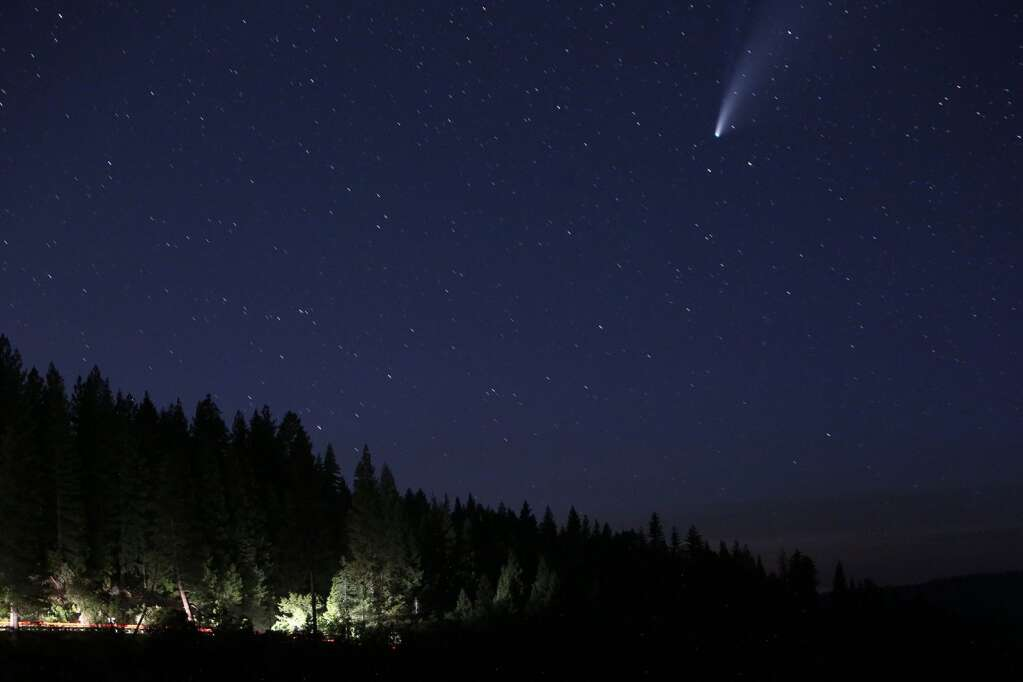 Vehicle traffic makes its way along Highway 20 east of Nevada City while the comet Neowise makes its way along the northwestern skyline as viewed from the Jefferson Creek Scenic Overlook. | Photo: Elias Funez