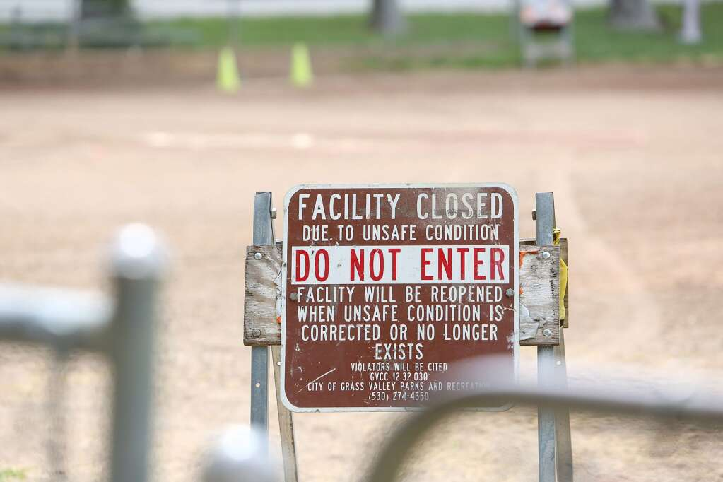 Multiple signs at Memorial Park's Les Eva Field remind those that it is not safe to enter due to Covid-19 in Grass Valley. | Photo: Elias Funez