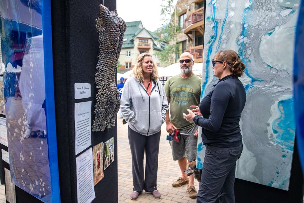 Breckenridge artist Andrea Kreeger, right, explains her painting process to patrons at the Keystone River Run Village Art Festival on Saturday, July 24. Kreeger is a local painter who collaborates with her partner, sculptor Levi Larkin. | Photo by Liz Copan / Studio Copan