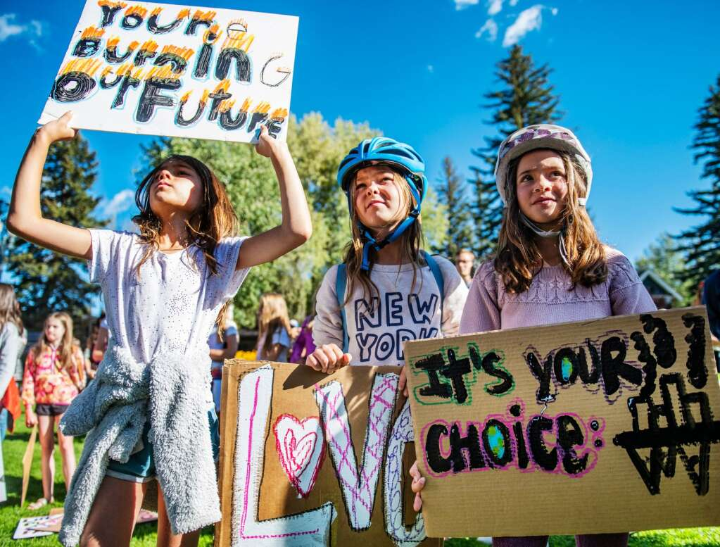 Aspen Country Day School 4th graders Sofia Abbaszadeh, 9, left, Bailey McDonough, 9, center, and Nell Lieb, 9, hold their signs in Paepcke Park as students give speeches during the Global Climate Strike event in Aspen on Friday, September 20, 2019. (Kelsey Brunner/The Aspen Times)