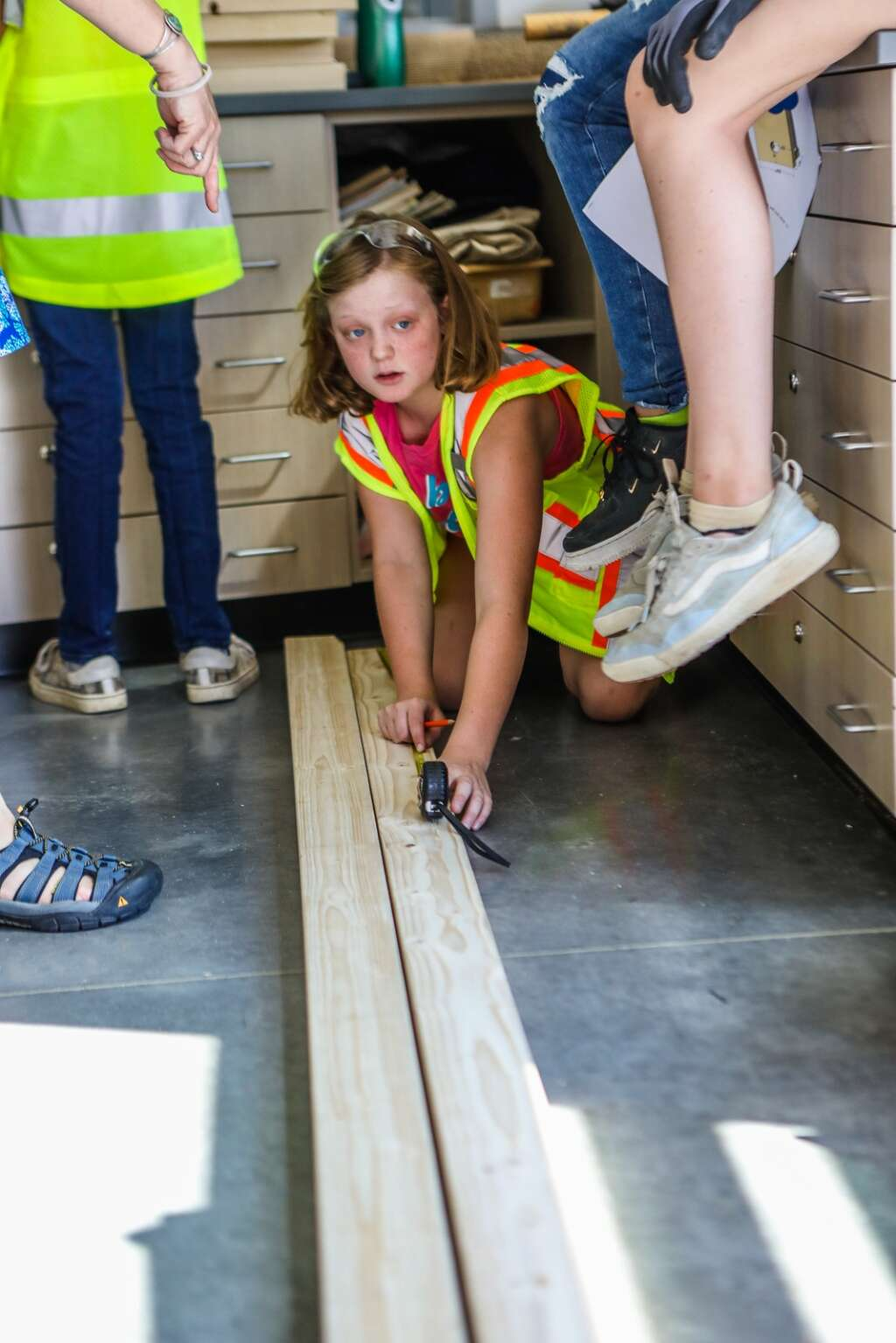 Amber Montgomery measures board lengths while constructing cornhole boards during YouthPower365 build day Friday at Eagle Valley Elementary School in Eagle.
