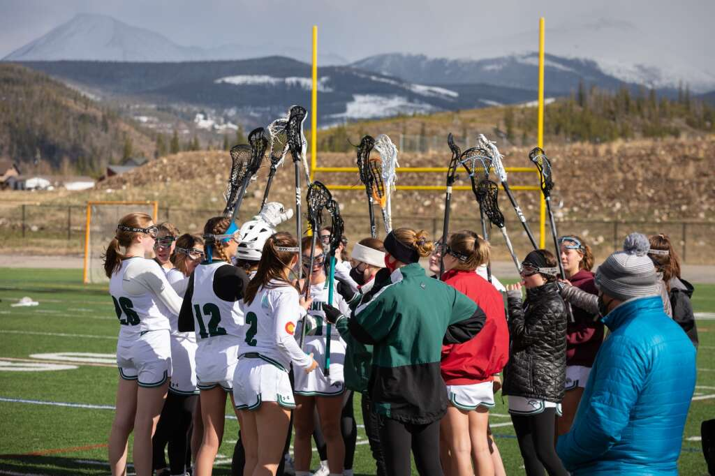 The Summit High School girls lacrosse team huddles during their 14-4 loss to Eagle Valley at Summit High School in Breckenridge on Tuesday, May 11, 2021. | Photo by Lucas Herbert / Lucas Herbert Media
