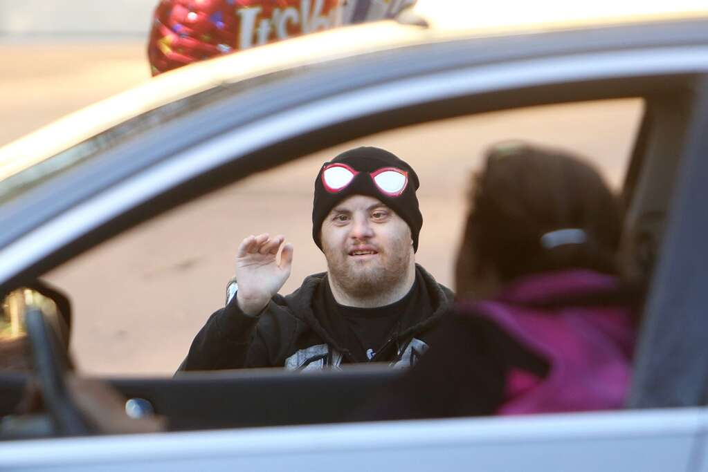 Skyler Monahan-Tonti waves to members of the community that turned up to wish him a happy birthday from in front of his Butler Street home in Grass Valley. Monahan-Tonti turned 33 Thursday Nov. 19. | Photo: Elias Funez