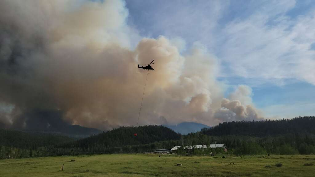 A fire helicopter picks up a bucket of water at the Hideaway Ranch off Routt County Road 16 to the east of the Gore Range where the fire is burning. The fire moved significantly to the southeast on Tuesday. (Photo by Dylan Anderson)