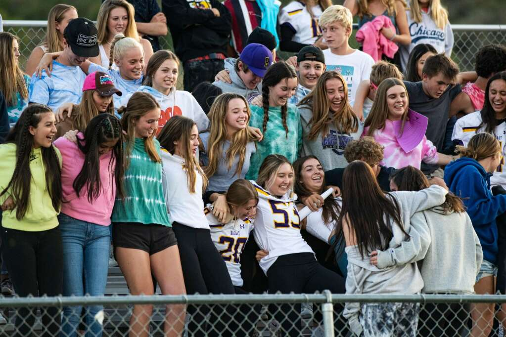 Basalt Students fall over in the stands while cheering for their team during the season opener against Woodland Park at Basalt High School on Friday, Aug. 27, 2021. (Kelsey Brunner/The Aspen Times)