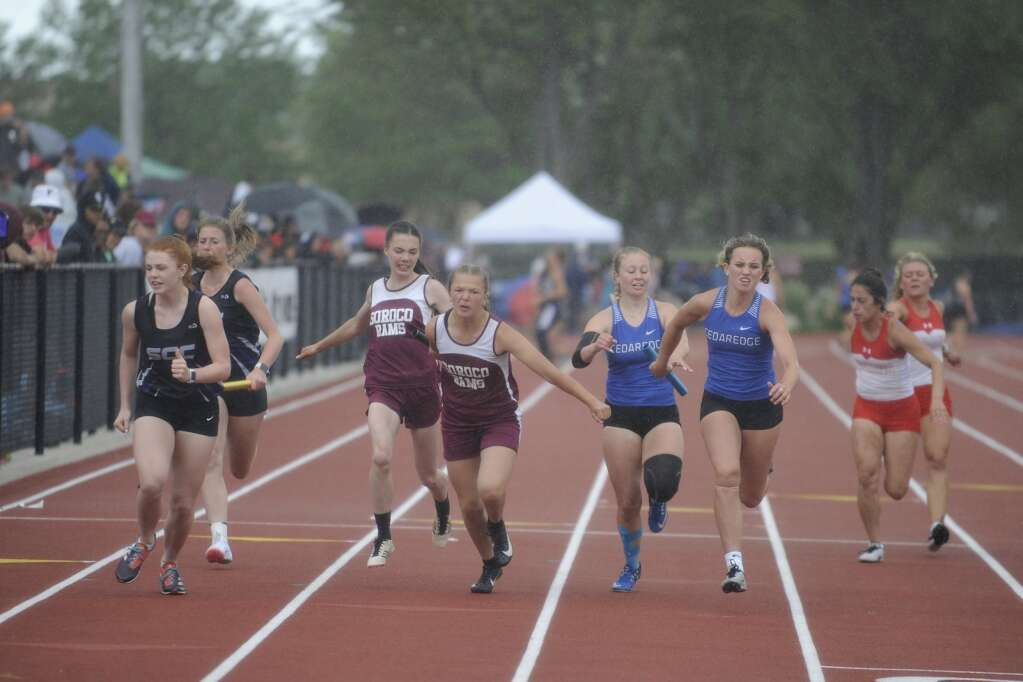 Soroco junior Marissa Martindale hands the baton to freshman Lexi Vandenburg during a rainy 4x100 race at the CHSAA State Track and Field Championships at JeffCo Stadium on Saturday. (Photo by Shelby Reardon)