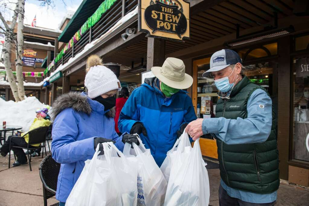 Rotarians Jeanne Woods, left, and Randy Woods pick up bags of soup and bread from Rob Robinson, right, at the Stew Pot in Snowmass Mall to take to residents at the Brush Creek Lot Safe Outdoor Space Friday, Feb. 19, 2021. (Kelsey Brunner/The Aspen Times)