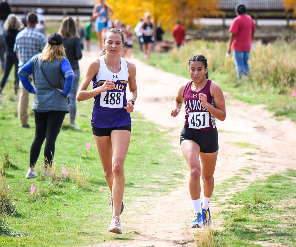 Basalt High School's Katelyn Maley, left, battles with Alamosa's Sarah Delacerda during Friday's Class 3A Region 1 cross country meet at VIX Park in New Castle.   Chelsea Self/Glenwood Springs Post Independent