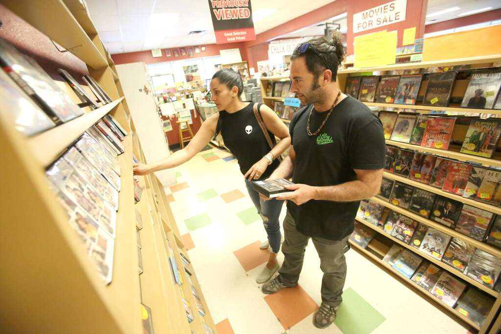Peter and Deyra look for the perfect movies from the shelf Friday afternoon at Grass Valley's Video Library. After publishing that the store was in the process of closing, interest in purchasing the store and keeping it open has surfaced from interested parties. The video store has since closed. | Photo: Elias Funez