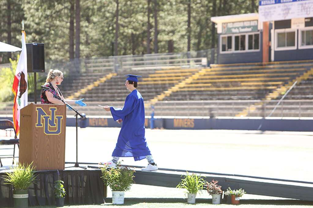 A Nevada Union High School graduate hands his name off to be read aloud to an empty Hooper Stadium during Wednesday's drive-thru ceremony. | Photo: Elias Funez