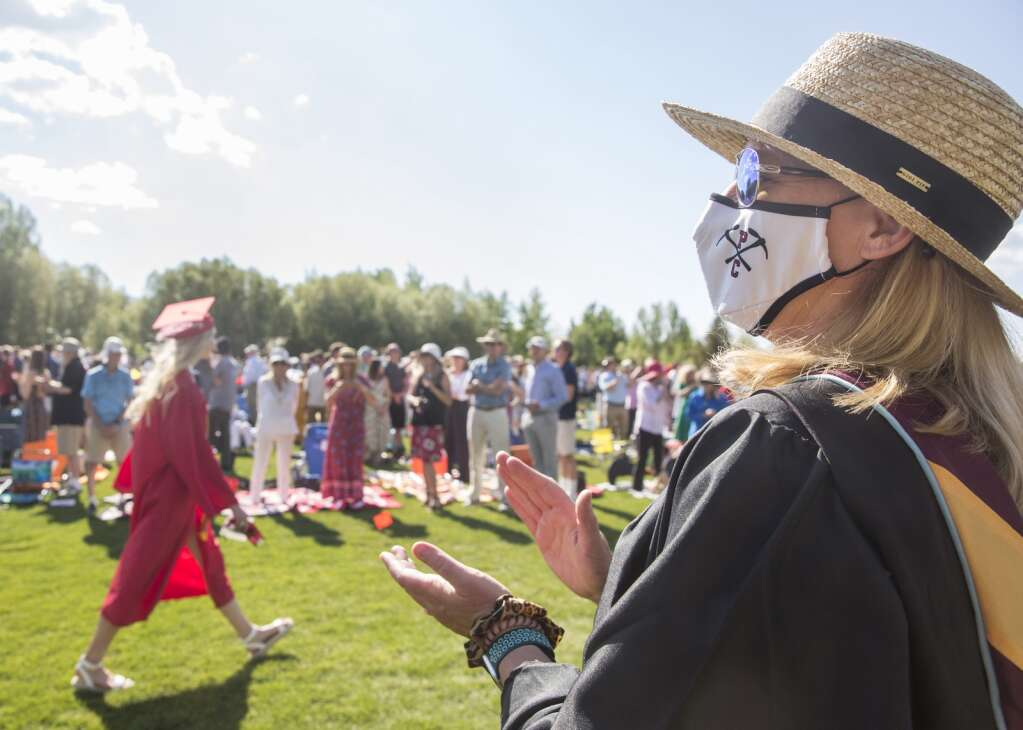Amie Campbell, assistant principal at Park City High School, applauds graduates as they process into the bleachers on the North 40 playing fields Thursday evening, June 3, 2021. Face masks were recommended, not required, during the ceremony. (Tanzi Propst/Park Record)
