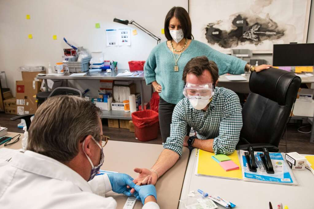 Dr. Jason Hicks takes a blood sample to test Isaac Flanagan for COVID-19 antibodies in the lab at Aspen Covid Testing on Friday, Jan. 22, 2021. (Kelsey Brunner/The Aspen Times)
