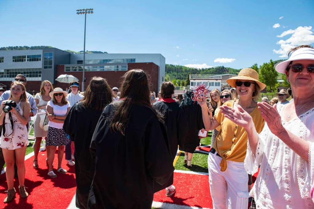 Family and friends of Aspen High School graduates cheer them on as they process out of the football stadium after the commencement ceremony on Saturday, June 5, 2021. (Kelsey Brunner/The Aspen Times)