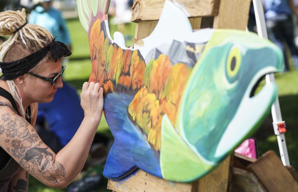 Trisha Bellefuille paints a fish panel on Saturday, Sept. 4, 2021, at the Art in the Park festival in Granby. Bellefuille won second place at the first ever Granby arts festival.   Eli Pace / Sky-Hi News