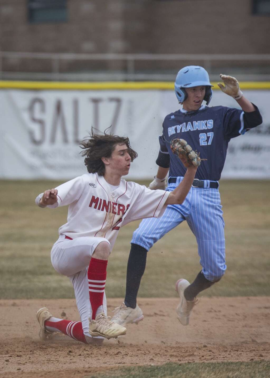 Park City's Dylan Fishbough (23) lunges to catch the ball, striking out Salem Hills' Luke DeGraffenried (27) during their matchup Monday afternoon, April 5, 2021. The Miners fell to the Skyhawks 7-2. (Tanzi Propst/Park Record)