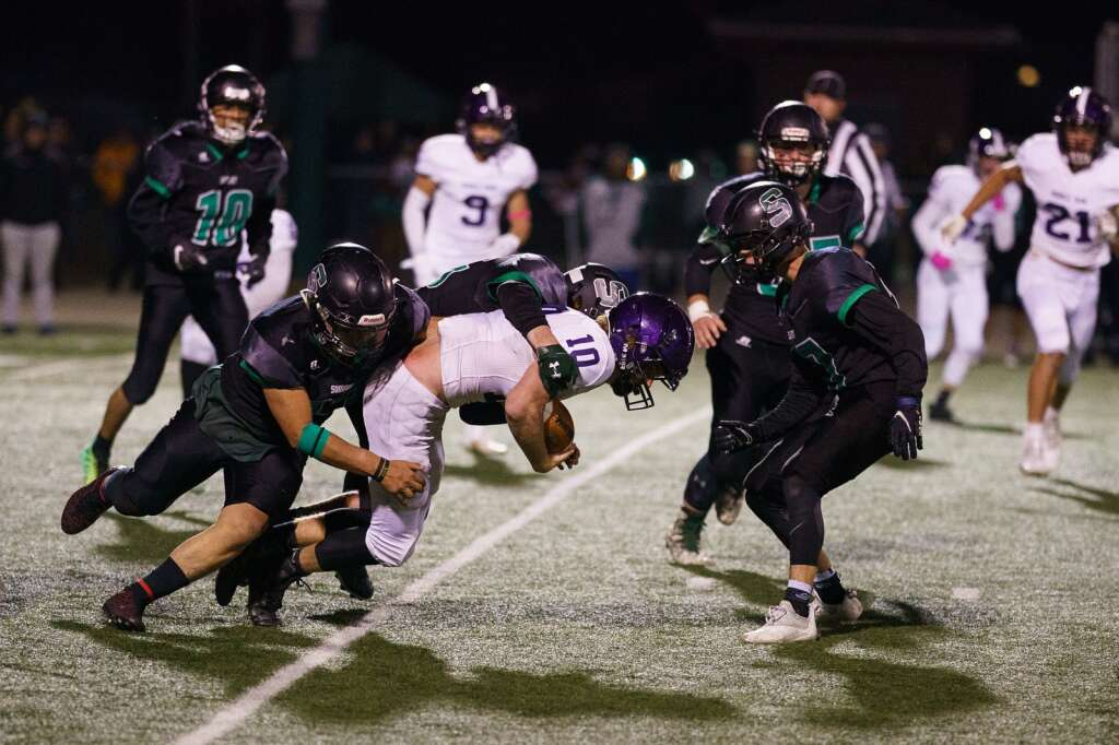 Jackson Segal, left, and Keaton Smith take down Middle Park quarterback Davis Emery late in the fourth quarter of the Tigers' homecoming win against the Middle Park Panthers on Friday, Sept. 24, at Tiger Stadium in Breckenridge. | John Hanson/For the Summit Daily News